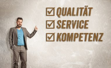 Businessman pointing up towards text, Quality, Service, Competen