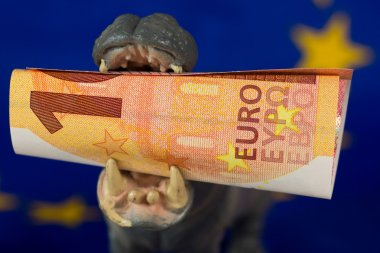 10 Euro note in mouth of a hippo figurine