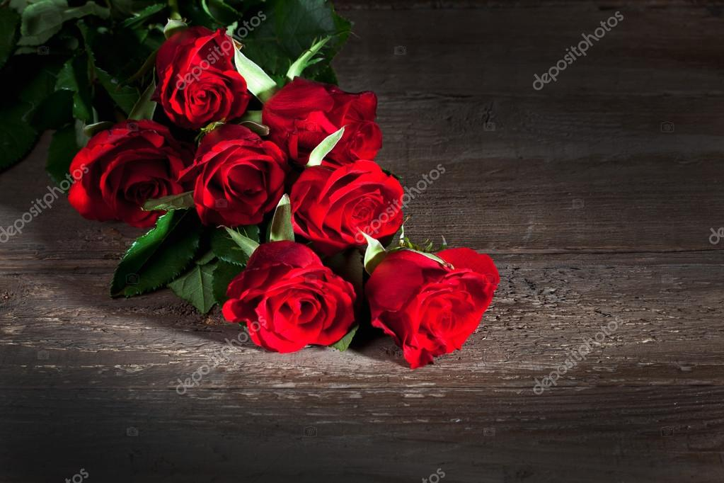 Red roses, wooden background