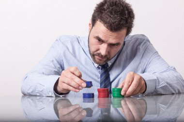 Mature man with poker chips on glass table, sorting stacks