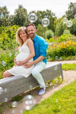 Happy couple expecting baby, sitting on bench in park