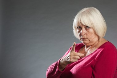 Altere Frau zeigt warnend mit dem Finger