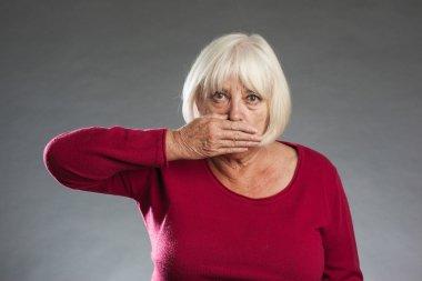 Female senior holding hands over mouth.