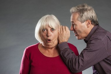 Senior couple, man whispers into ear of woman, she looks surprised.