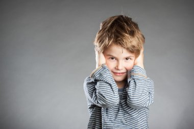 Portrait of boy, hear no evil, grey background