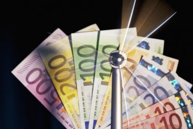 Spinning windmill in front euro notes
