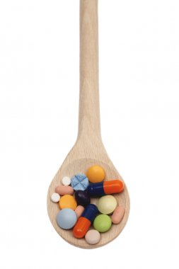 Tablets on wooden spoon