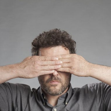 Mature man covering eyes