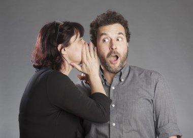 Mature couple woman whispering secret in man's ear