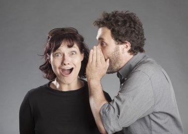 Mature couple man whispering secret in woman's ear