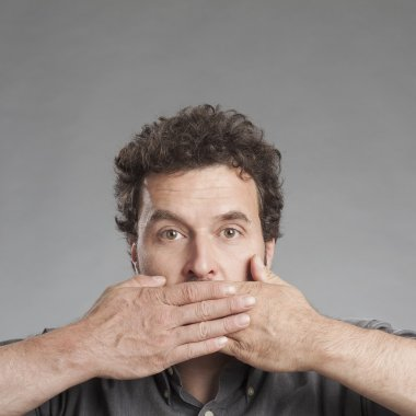 Mature man covering mouth