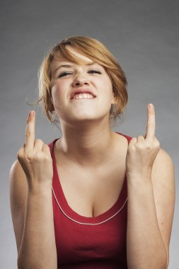 Teenage girl in red tank top showing obscene gesture against gray background