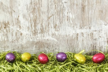 Colorful chocolate eggs on artificial grass