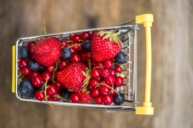 cart with strawberries, blueberries and redcu