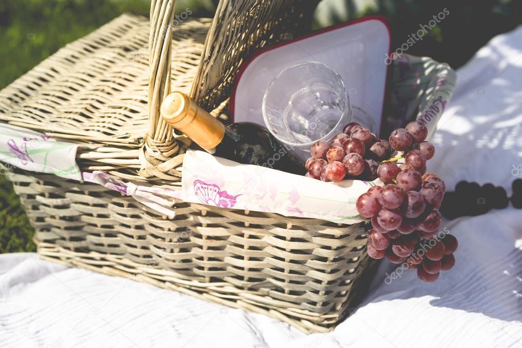 Picnic basket, blanket, wine glass and grapes