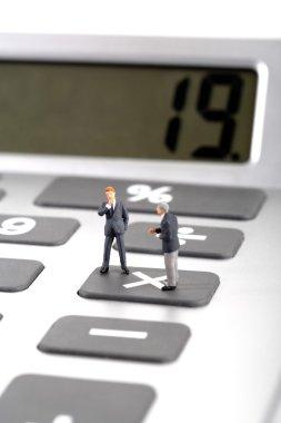 Figurines of businessmen on calculator