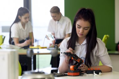 Teenage Girl Working on Robotic Arm