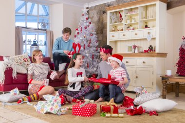 Family opening presents at Christmas Time