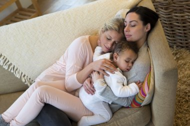 Female couple sleeping with their son