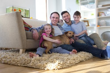 Male couple posing with son, daughter and dog