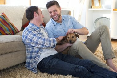 Male couple sitting with their pet dog