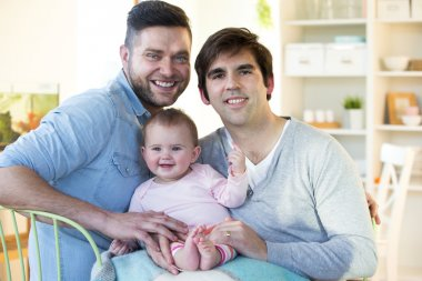 Male couple posing with their daughter at home