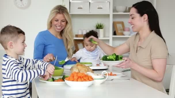 Weibliches Paar beim Abendessen mit ihren Kindern