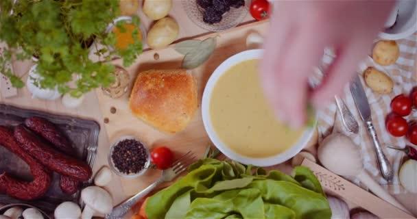 Polévka v misce mezi různými složkami rozmanité na dřevěném stole
