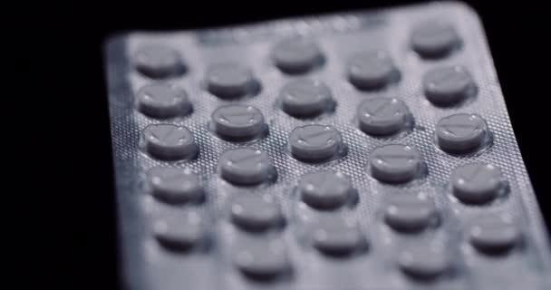 Blister mit Medikamenten auf schwarzem Hintergrund.