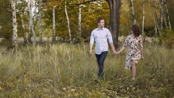 Fiatal pár sétál a réten. Pozitív fiatal Poeple Boldogság.