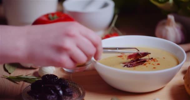Žena zdobení polévka s masem na stole