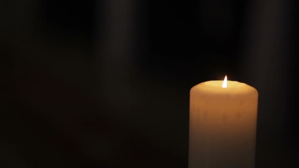 Candle on the black background