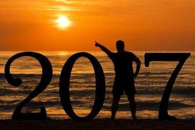 Man Silhouette year 2017 at sunrise at sea