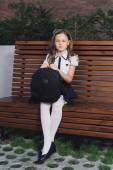 Photo schoolgirl in uniform waiting for the bus to school