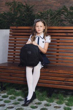 schoolgirl in uniform waiting for the bus to school