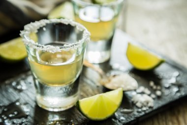 Gold tequila shots on rustic wood background
