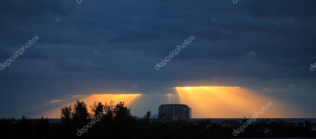 Golden sun rays bursting through the dark blue clouds