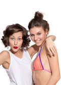 Two girls, young beautiful caucasian female brunette models in shirt, jeans shorts, swimwear posing with expressive emotion, exited, shocked, surprised isolated on white, retouched portrait