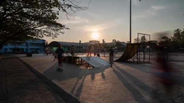 Time Lapse Group of Girls and Boys play Skateboards and rollerblades in the park at sunset. Beautiful Young People Skateboarding.Outdoor sports are popular in phuket Thailand