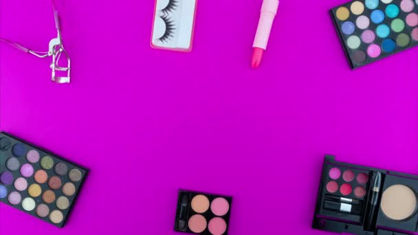 Multicolored beautiful eyeshadow palette and Various cosmetic accessories for makeup on pink background Beauty products Makeup cosmetic Summer eye shadow Stop motion animation Looping video timelapse