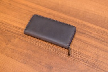 Brown leather wallet on the wooden table. Unisex wallet.