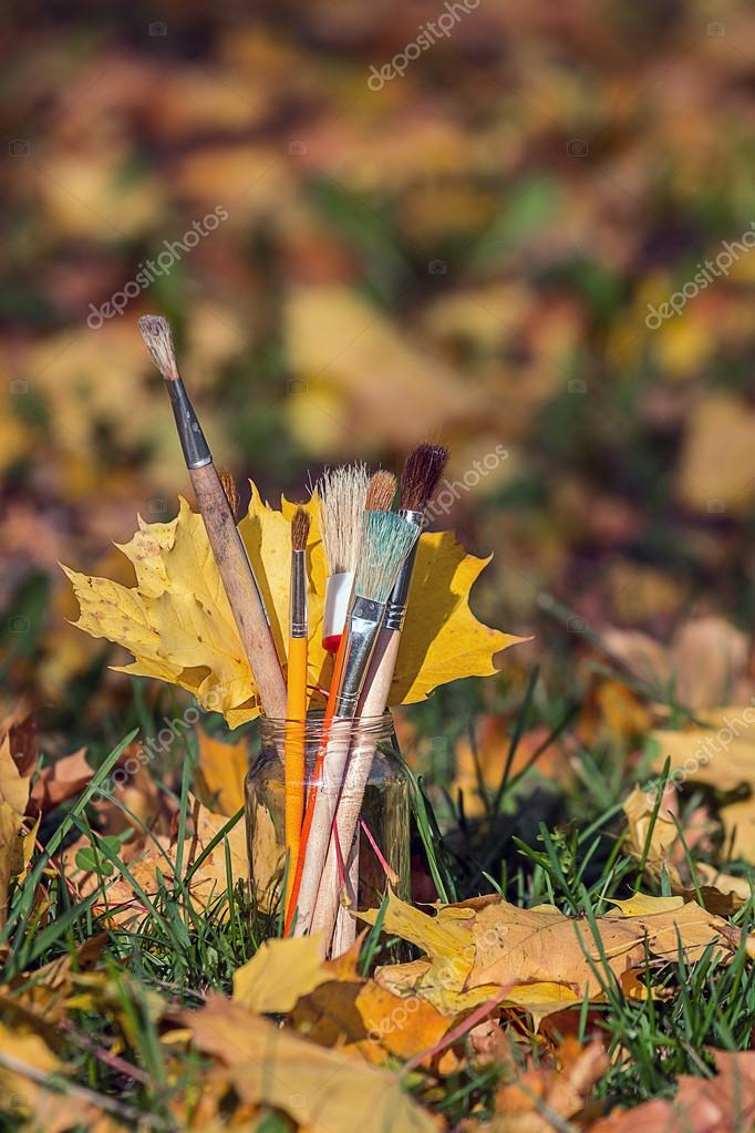 brushes in a glass with a yellow maple leafs