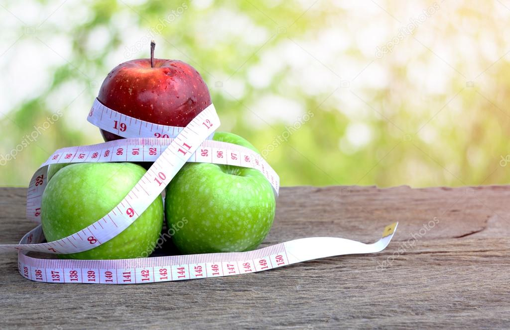 Red apple and green apple with measuring tape.