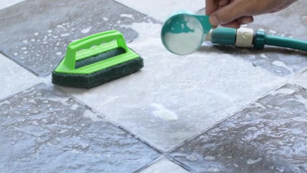 Close up a human hand pours detergent onto the wet tile floor to clean it.