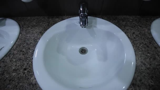A man approaches the tap opens the tap, the water begins to flow, hand washing