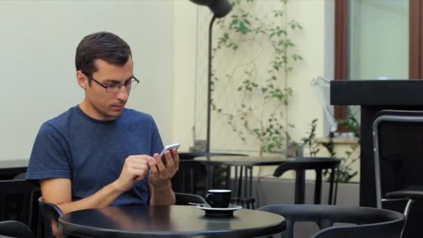 A man sits at a table in the cafe and uses the phone