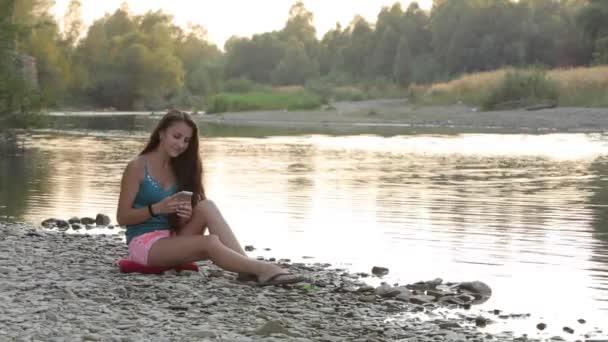lány ül a folyóparton, a telefon e-mail megtekintés