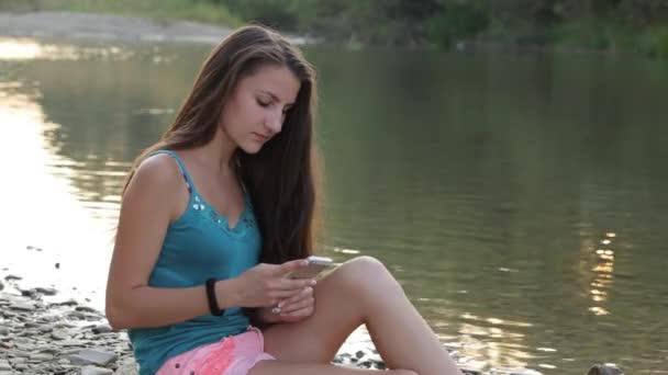 lány, a folyó partján, a telefon gépelés ülve