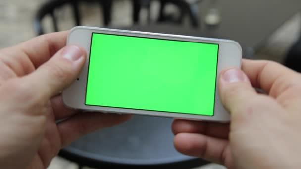 Chytrý telefon Held ručně. Zelená obrazovka Chroma klíč sledování pohybu vertikální. Člověk sedí telefon na animace otáčení rukou