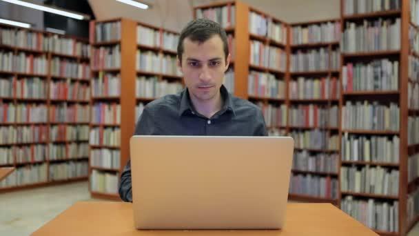 Mladý pohledný muž sedí a pracuje na notebooku